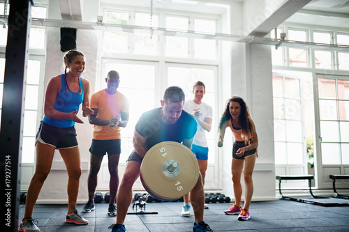 Fit man lifting weights with friends clapping in the background