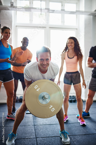 Smiling man lifting weights with friends watching in the backgro