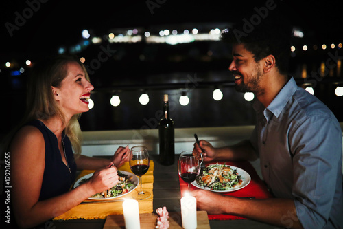 Young beautiful couple having romantic dinner on rooftop - 179286555