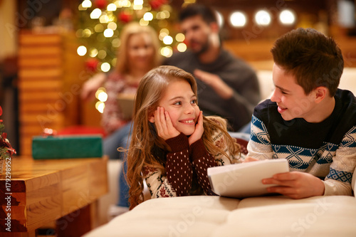 Girl with boy write holiday wishes on paper