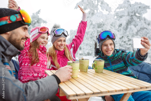 Skiing family in cafe making photo while resting