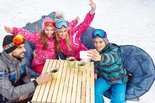Boy taking family selfie in cafe on ski terrain