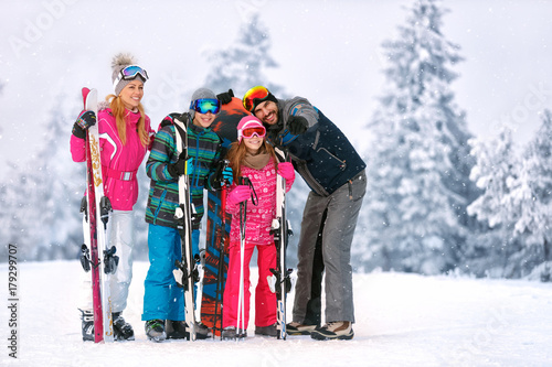 Family with ski equipment looking something together