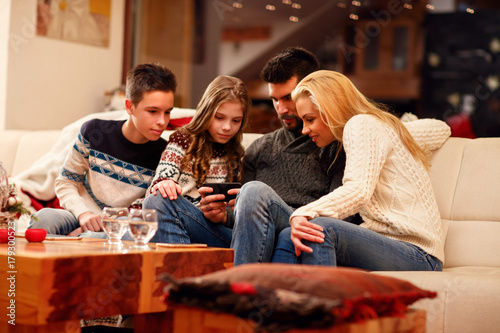 family playing game on mobile phone on Christmas holidays.