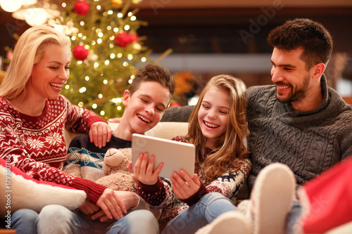 Christmas time- family watching funny video on digital tablet.