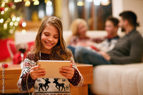 little girl with tablet and headphones at home.