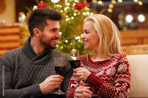 couple celebrating Christmas toasting with glasses of red wine.