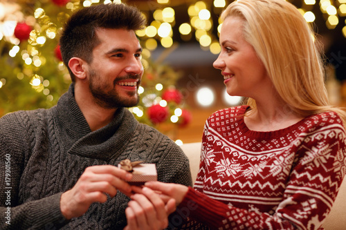 romantic man suprise woman with gift for Christmas.