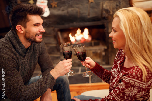 woman and man toasting delicious red wine at romantic fireplace.
