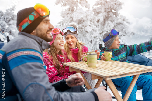 Family laughing and takes tea break during skiing on the mountain