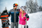 couple skiing and snowboarding enjoying in snowy mountains together