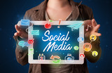 Woman holding tablet with social media graphics