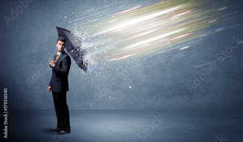 Business man defending light beams with umbrella concept