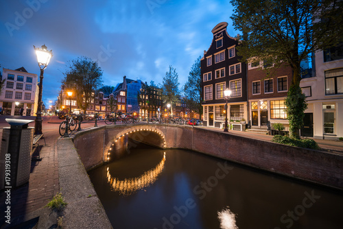 Foto op Plexiglas Amsterdam Magical effect of night lights on bridge reflected in calm water of Amsterdam canal lined with typical buildings