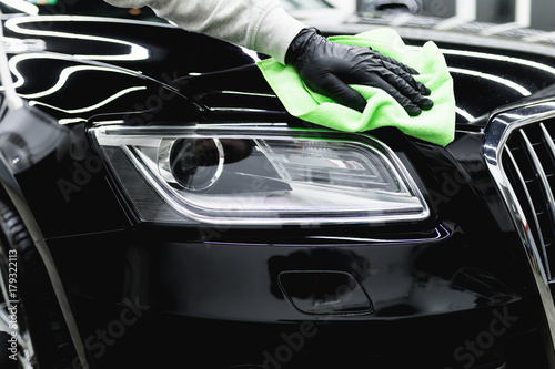 A man cleaning car with microfiber cloth, car detailing (or valeting) concept. Selective focus.  - 179322113