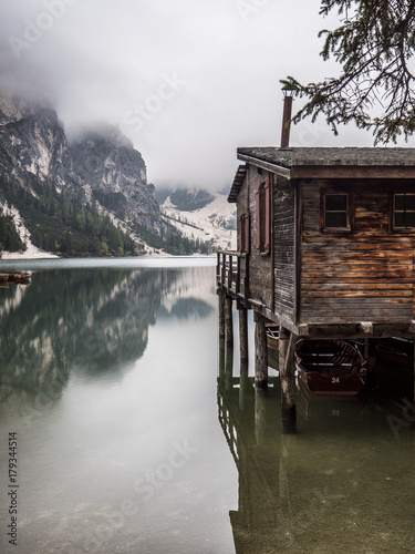 Foto op Plexiglas Bergen View to beautiful calm lake in forest in mountains, with a wooden hut, cabana or small house on the water