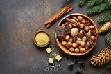 Nuts and christmas spices in a wooden bowl on a dark slate,stone or metal background.Top view with copy space.
