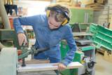 female carpenter using electric sander for wood - 179348168
