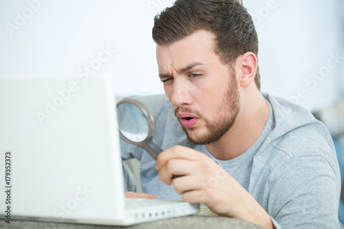 Poster man work on laptop with magnifying glass