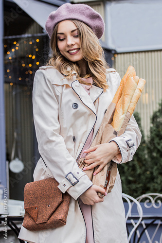 Sticker So tender and beautiful. Vertical shot of magnificient blonde woman keeping baguettes in hands and smiling while posing against french vintage cafe. French fashion woman. French style and beauty.