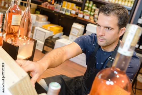 Fototapeta Shop assistant in liquor store
