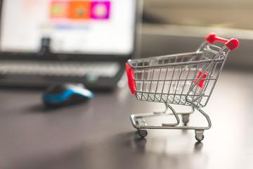 Mini Einkaufswagen mit Laptop im Hintergrund, Onlineshopping