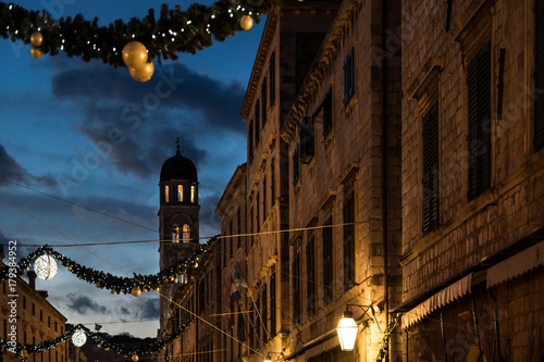 Fototapeta Stradun old street with bell tower decorated with Christmas lights and ornaments at dawn, Dubrovnik, Croatia