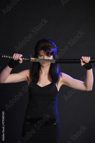 Girl with Katana in the studio against black Poster