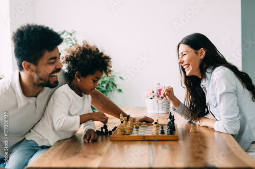 Poster Happy family playing chess together at home