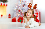 child girl writing letter santa home near Christmas tree