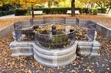 Ancient fountain in  autumn park with decorative fence