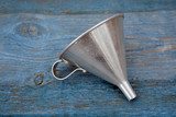 Vintage metal funnel with handle on old wooden  table