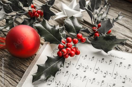Fotobehang Muziek Alte handgeschriebene Musiknoten mit Ilex Zweig, roten Beeren und roter Weihnachtskugel, Weihnachten, xmas