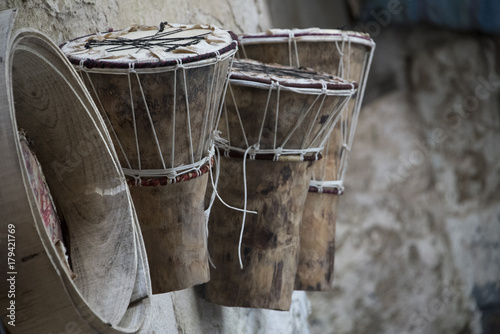 Aluminium Marokko African drums(Djembe) and drum frame hung on wall outside of craftsman's workshop