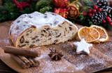 Weihnachtlicher Butterstollen mit Rosinen auf Holztisch mit Gewürzen und Puderzucker - 179425950