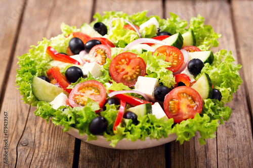 bowl of fresh salad on a wooden table - 179439367