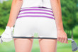 Golf club in woman hands on ass background on a background of golf courses