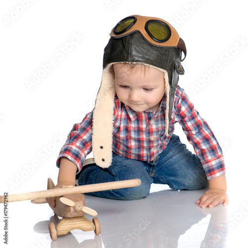 A little boy in a pilot's cap and a wooden plane in his hand