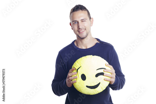 Man standing over a white background, holding a winking emoji plush Poster