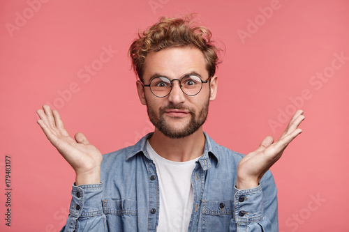 Bearded Caucasian male has hesitatnt and displeased expression, gestures doubtfully, has no answer on difficult question, being puzzled or confused Plakat