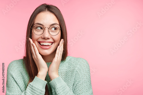 Happy dreamful Asian young woman with attractive appearance, charming broad smile looks aside, dreams about new purchases, isolated over pink background for your advertisment or promotional text.