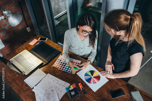 Two creative female designers choosing colors working with colour palette in the Poster