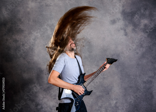wild musician with black guitar and flying hair Poster