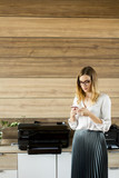 Young businesswoman with mobile phone in office - 179512783