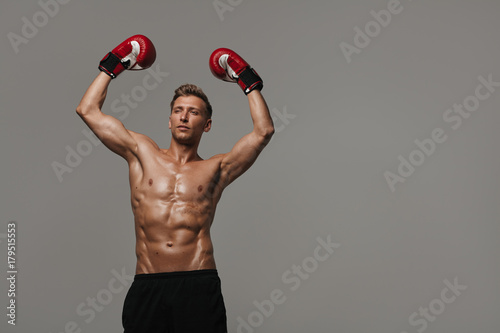 Sportive man posing in boxing gloves Poster