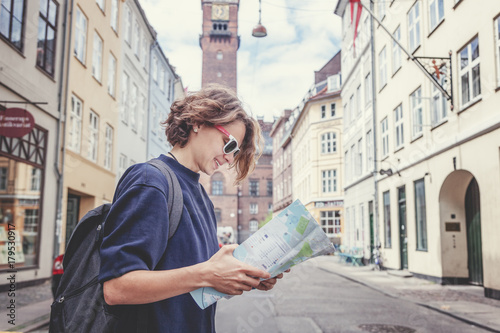 Happy young woman traveler with map in hand on the background of a European city