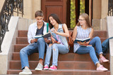 Young students studying while sitting on stairs outdoors