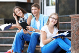 Students reading while sitting on stairs outdoors