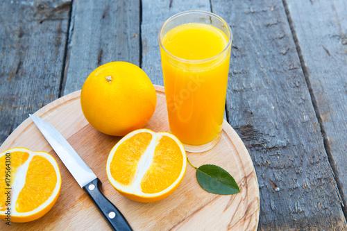 Fotobehang Sap Orange juice in glass with fresh fruits orange cutting board on wooden background