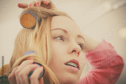 Fotobehang Kapsalon Woman curling her hair using rollers